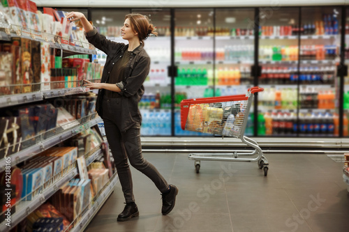 Concentrated young woman in supermarket choosing products.
