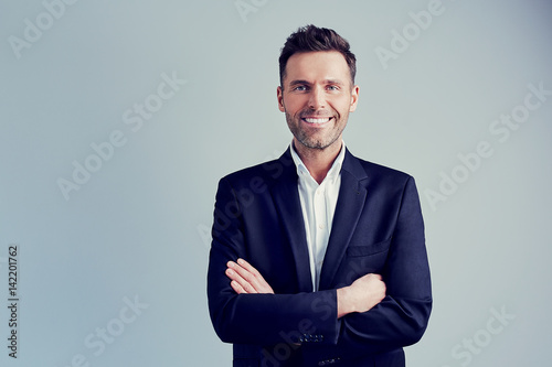 Fotografie, Obraz  Happy businessman isolated - handsome man standing with crossed arms