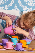Little Girl Playing Toy Baby Dishes At Home