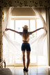 young woman opening curtains in a bedroom at hotel room before to go outdoors