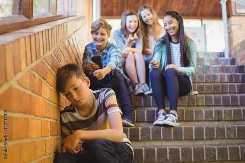 School friends bullying a sad boy in school corridor Canvas Print