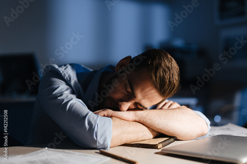 Photo Portrait of exhausted man falling asleep at workplace in dark room late at night
