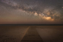 Boardwalk Leading To The Ocean Under The Night Sky
