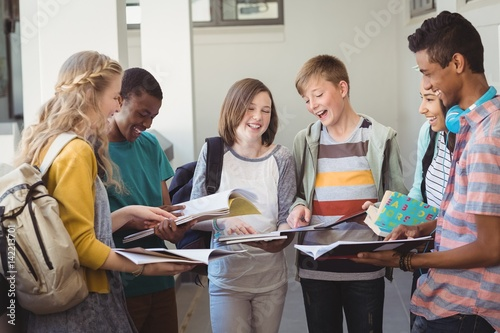 Fotografía  Group of smiling students standing with notebook in corridor