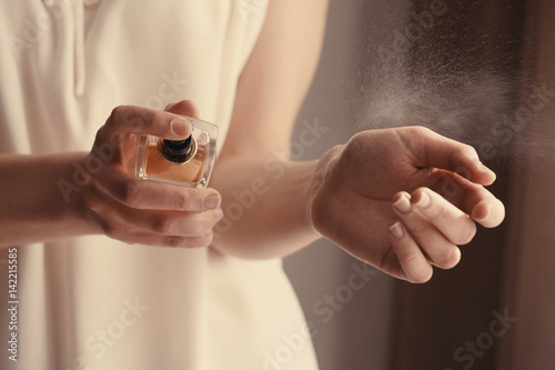 Obraz Beautiful young woman with bottle of perfume at home, closeup - fototapety do salonu