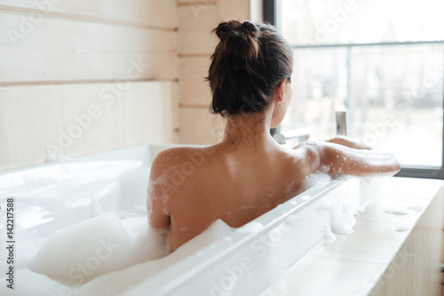 Slika na platnu Young woman having bubble bath and looking at window