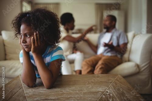 Fotografiet  Sad girl listening to her parents arguing