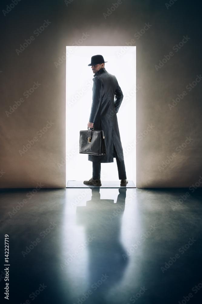 Fototapeta Man silhouette standing in the light of opening door in dark room