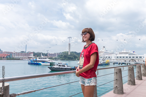 Photo  Young woman in Singapore harbor. Cloudy day.