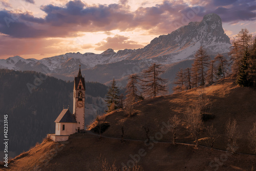 Photo Stands Chocolate brown dolomites mountain church at sunset