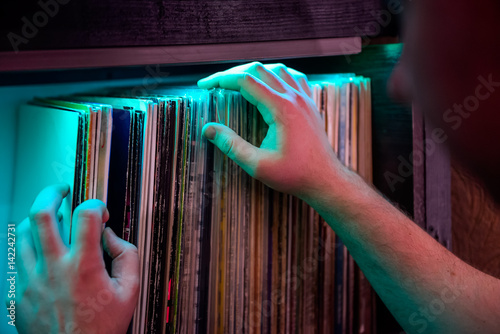 Spoed Foto op Canvas Muziekwinkel Close up man's hands browsing through vinyl records collection. Music background. Selective focus