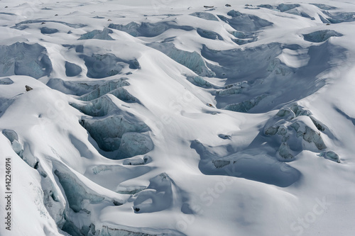 Valokuvatapetti Detail of glacier flow and crevasses covered by snow in winter