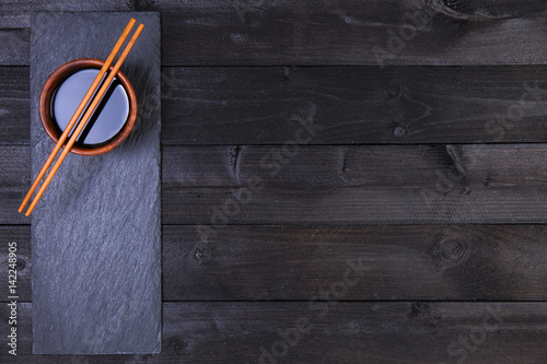Background for sushi. Soy sauce, chopsticks on black table. Top view with copy space