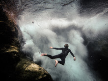 Man Floating In Front Of Underwater Waterfall