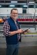 Smiling factory worker using digital tablet