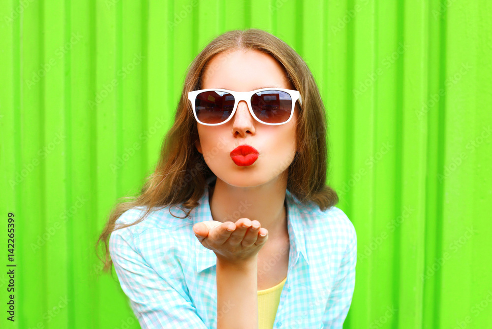 Fototapety, obrazy: Fashion portrait pretty woman in white sunglasses sends an air kiss over colorful green background