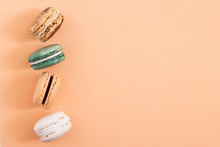 Row Of Colorful French Macaroons On Blue Background. Top View, Copy Space For Text. Social Media, Blogging Concept