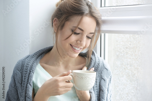 Poster The Beautiful young woman drinking tea near window at home