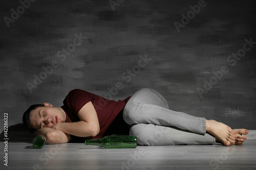 Tablou Canvas Handsome depressed man lying on floor with bottles at home