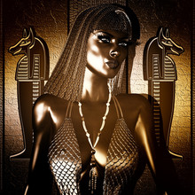 Beautiful Black Egyptian Queen Or Pharaoh With Gold Crown, Fashion Cosmetics, Statue Earrings Posing Against A Stone Textured Wall With Hieroglyphics.