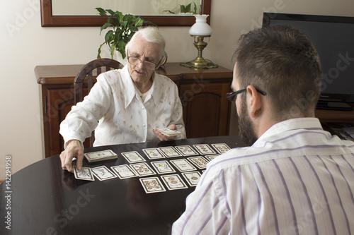 Naklejka premium Wiekowa wróżka stawia karty tarota. Bardzo stara kobieta stawia karty tarota mężczyźnie. Wróżenie z kart tarota.