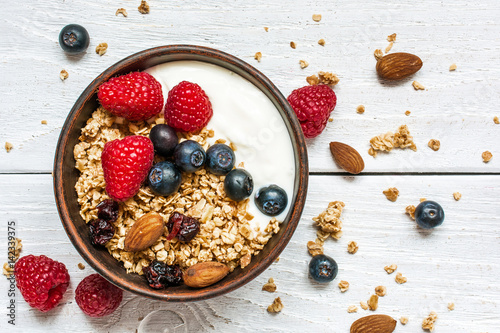 bowl of oat granola with yogurt, fresh raspberries, blueberries and nuts