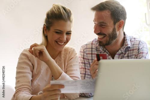 Fotografia, Obraz  Cheerful couple paying bills.
