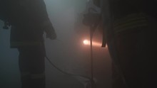 Firefighters With Hoses And With Flashlight In Dark Room