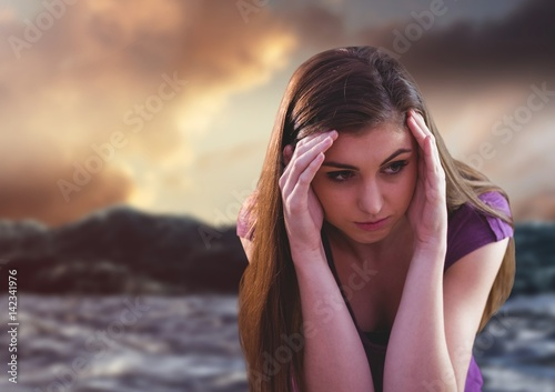 Sad young woman in against csunset and ocean