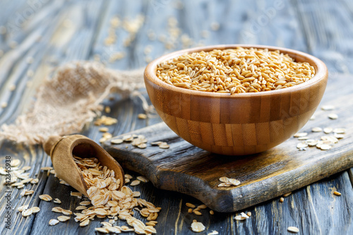 Whole oats in a bowl and oat flakes in a wooden scoop.