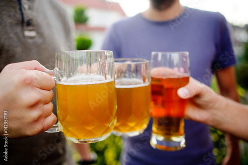 Fotografia  Three young men cheerfully spend time behind a glass of beer