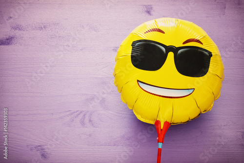 Photo  image of cute smiling emoticon wearing black sunglasses, emoji concept