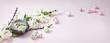 Wielkanocne gniazdko z jajeczkami i wiosenne kwiaty na różowym i pastelowym tle, happy easter, wesołych Świąt