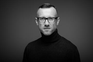 portret mężczyzny w studio na ciemnym tle w okularach