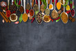 Various spices spoons on stone table. Top view .