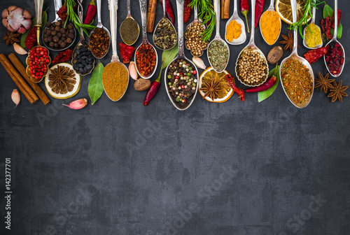 Foto op Plexiglas Kruiden Various spices spoons on stone table. Top view .