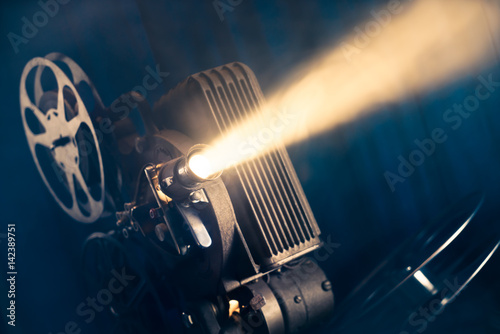 Photo  movie projector on a wooden background with dramatic lighting and selective focu