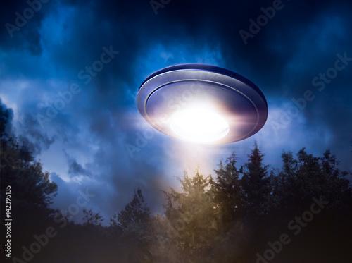 Fototapeta Wysoki kontrast obrazu UFO lecący nad lasem z wiązki światła w nocy