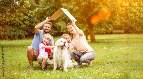 Fotografie, Obraz  Familie mit Dach über Kopf als Symbol für Hausbau