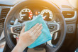 Hand with microfiber cloth cleaning car.woman cleaning car interior - car detailing and valeting concept in car wash car care station ,selective focus,vintage color