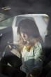 Sad girl inside the car using her smarthphone