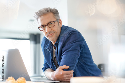 Photographie  Handsome 45-year-old man at home connected on laptop