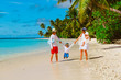 family with kids playing walking on tropical beach