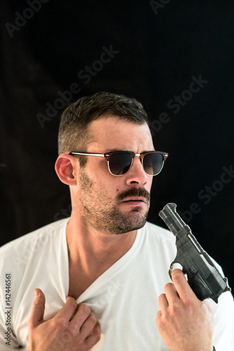 Young man with eyeglasses looking scared at his handgun плакат