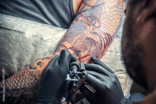 Photo Tattoo specialist works in tattoo studio