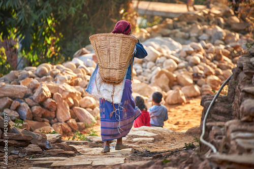 Fotografie, Obraz  Nepalese woman carries huge wicker basket on her back at the street of Bandipur,