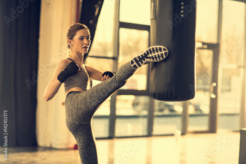 Fotomural young sportswoman kicking punching bag in sports center