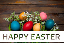 Multi-colored, Bright Easter Eggs With Green, Spring Lilies Of The Valley On Wooden Background With White Rectangle And The Text Of Happy Easter