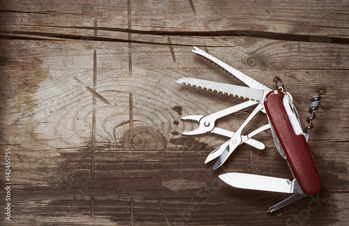 Valokuva  old Swiss knife on a wooden background