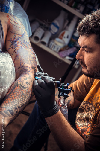 Professional tattooer makes tattoo in tattoo parlor Canvas Print